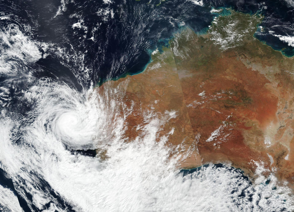This Sunday, April, 11, 2021, satellite image released by NASA shows Tropical Cyclone Seroja hitting the coast of Western Australia. People living on the coast were preparing themselves Sunday for the landfall of Seroja. (NASA Worldview, Earth Observing System Data and Information System (EOSDIS) via AP)
