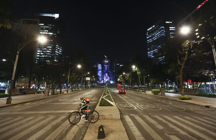 A food delivery worker crosses Reforma Avenue, normally congested with traffic, in Mexico City, Friday, March 27, 2020. City authorities announced measures to deal with the new coronavirus such as closing bars, discos, museums, zoos, cinemas, theaters and gyms. (AP Photo/Eduardo Verdugo)