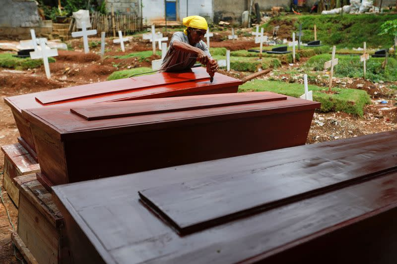 Suherman, a 45-year-old coffin maker, prepares coffins ordered to be donated for the coronavirus disease (COVID-19) victims at a workshop inside a funeral complex in Jakarta