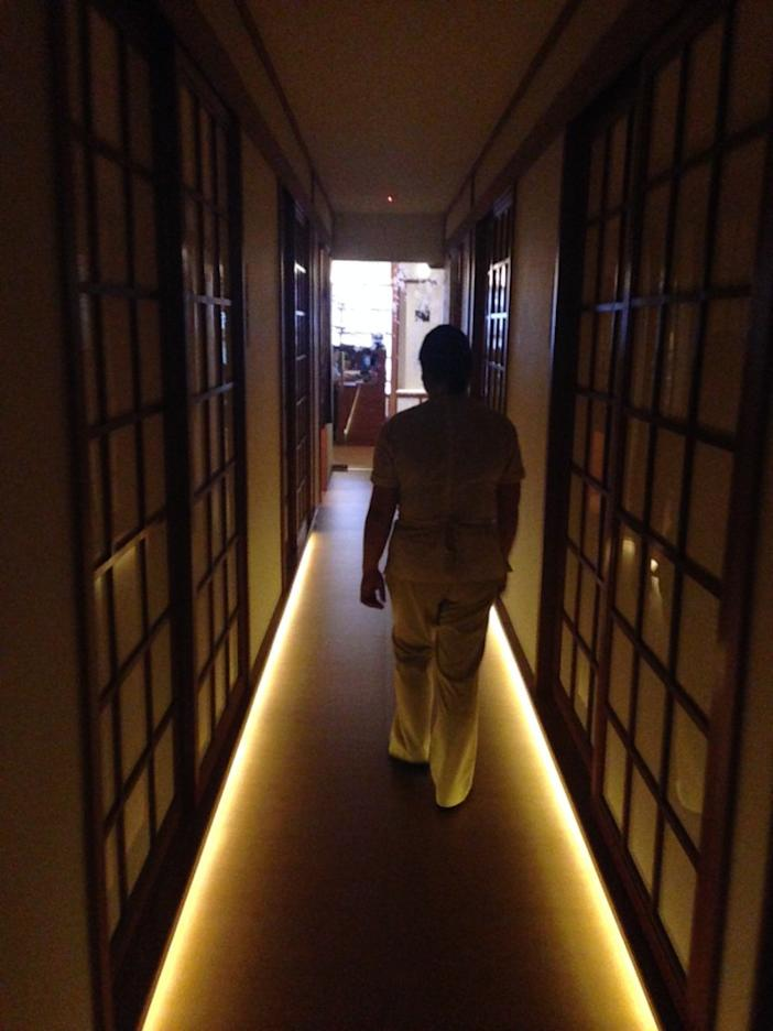 Being led down a dimly lit hallway to my changing room. Image Credit: Gayle