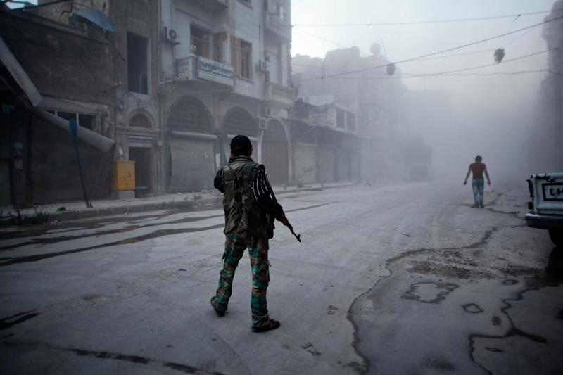 A rebel fighter stands on a street covered with dust following a reported air strike by Syrian government forces in the old city of Aleppo on July 21, 2014 (AFP Photo/Ahmed Deeb)
