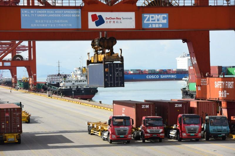 Shipping containers and cargo vessels are seen at the Dachan Bay Terminals in Shenzhen