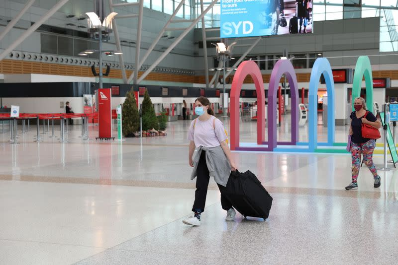 People wearing masks walk through Sydney Airport in the wake of a COVID-19 outbreak in Sydney