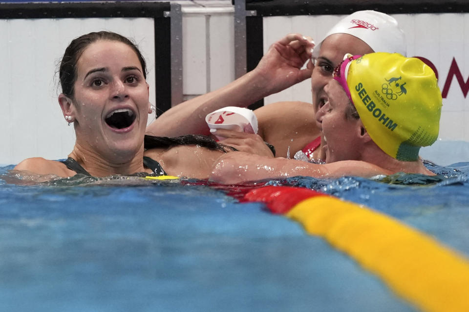 Kaylee McKeown, left, of Australia is congratulated by compatriot Emily Seebohm, right, and Canada's Kylie Masse after winning the final of the women's 100-meter backstroke at the 2020 Summer Olympics, Tuesday, July 27, 2021, in Tokyo, Japan. (AP Photo/Matthias Schrader)