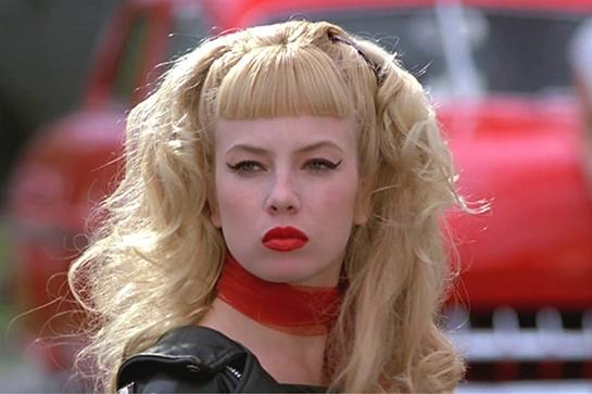 """<em><h2>Cry Baby (1990)<br></h2></em>Who needs <em>Grease</em> when you have <em>Cry Baby</em>, John Waters' demented ode to teenage toughs and the squares they occasionally love? In it, Traci Lords plays the gum-snapping delinquent of every rockabilly dude's dream — so what if she has bougie parents? The flicked eyeliner, leather jacket, chiffon neckerchief, and ever-present sneer is a look worth copying forever. <span class=""""copyright"""">Photo: Courtesy of Universal Studios.</span>"""