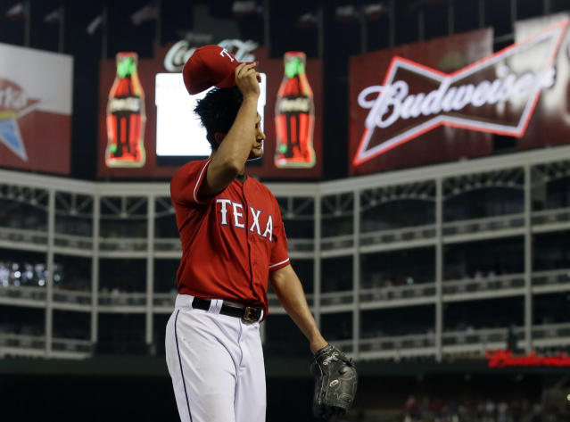 Texas Rangers' Yu Darvish of Japan acknowledges cheers by fans as he tips his cap on the way to the dugout in the ninth inning of a baseball game against the Boston Red Sox, Friday, May 9, 2014, in Arlington, Texas. Darvish had a no-hit bid through 8 2/3-innings in the 8-0 Rangers win. (AP Photo/Tony Gutierrez)