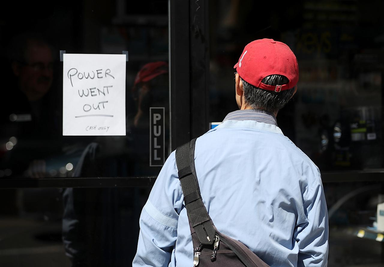 <p>A pedestrian looks at a sign posted on the door of a hardware store during a citywide power outage on April 21, 2017 in San Francisco, (Photo: Justin Sullivan/Getty Images) </p>