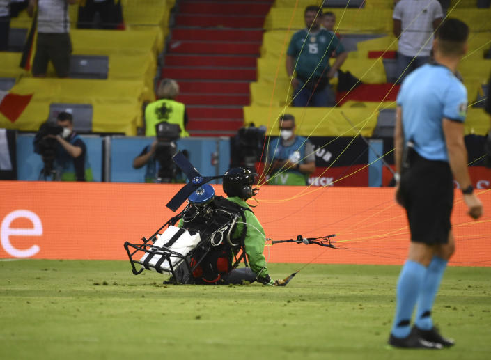 Referee looks as a paraglider lands on the pitch prior the start of the Euro 2020 soccer championship group F match between Germany and France at the Allianz Arena stadium in Munich, Tuesday, June 15, 2021. (Franck Fife/Pool via AP)