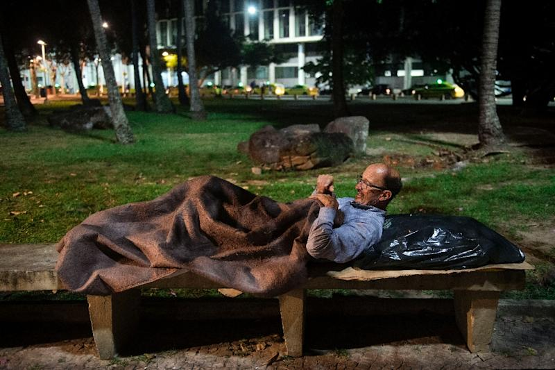 Vilmar Mendonca, who has worked as a human resources manager for several companies in Brazil and has been living on the streets for a year and a half, gets ready to sleep on a park bench in front of the Santos Dumont airport in Rio de Janeiro (AFP Photo/Mauro PIMENTEL)
