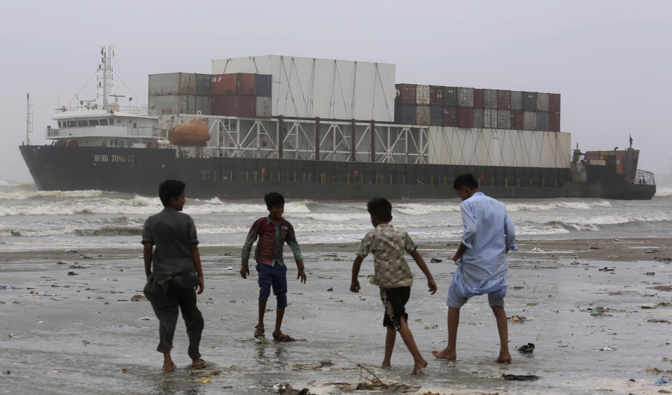 Youth play near the stranded Heng Tong 77 cargo ship at Sea View Beach near the southern port city of Karachi, Pakistan, Monday, July 26, 2021. Pakistani authorities said they are working on plans to refloat the cargo ship that ran aground last week amid bad weather en route to Istanbul from China. (AP Photo/Fareed Khan)