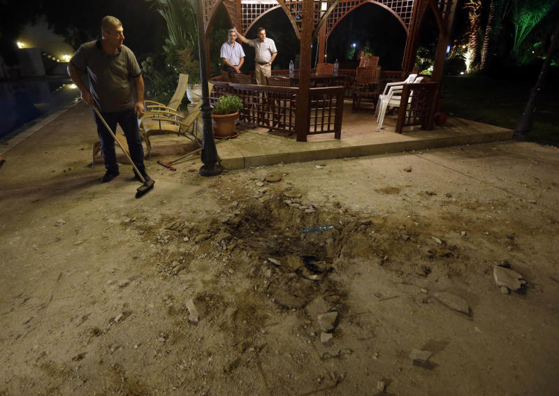 A Lebanese man, left, cleans next to a crater that left by a rocket attack at a villa few meters away from one of the entrances to the Lebanese presidential palace, in Fayadiyyeh area, eastern Beirut, Lebanon, early Friday, Aug. 2, 2013. At least two rockets slammed Thursday night into an area south of the Lebanese capital that houses the Defense Ministry and presidential palace, Lebanon's state-run news agency said. The attack comes on the same day when President Michel Suleiman gave a speech on the occasion of Army Day in which he criticized the involvement of the militant Lebanese Hezbollah group in the Syrian civil war in support of President Bashar Assad's forces. (AP Photo/Hussein Malla)
