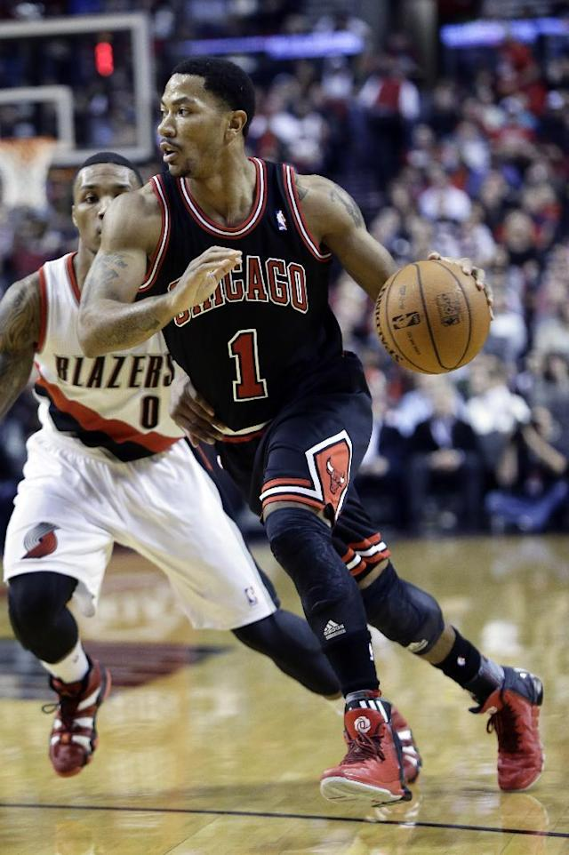 Chicago Bulls guard Derrick Rose, right, drives on Portland Trail Blazers guard Damian Lillard during the first half of an NBA basketball game in Portland, Ore., Friday, Nov. 22, 2013. Rose injured his right knee late in the third quarter and left the game. The Trail Blazers won 98-95.(AP Photo/Don Ryan)
