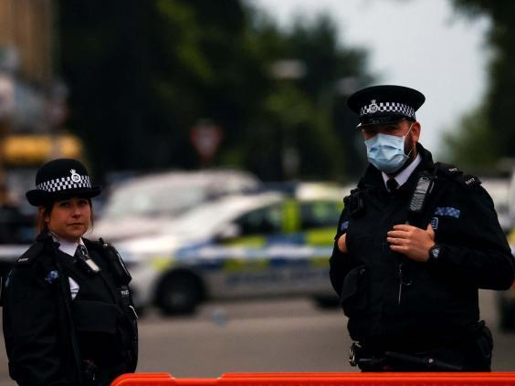 Police officers at the scene where a woman was shot by officers in Toxteth, Liverpool, 9 July 2020. (REUTERS)