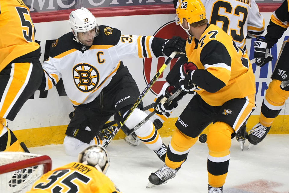 Boston Bruins' Patrice Bergeron (37) competes for the puck in the corner with Pittsburgh Penguins' Jeff Carter (77) during the first period of an NHL hockey game in Pittsburgh, Sunday, April 25, 2021.(AP Photo/Gene J. Puskar)