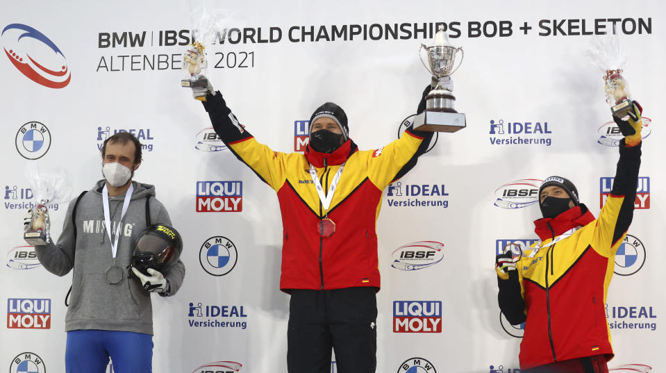 First place, Germany's Christopher Grotheer, center, holds the trophy on the podium after the men's skeleton race at the Bobsleigh and Skeleton World Championships in Altenberg, Germany, Friday, Feb.12, 2021. At left is second place Russia's Alexander Tretiakov and at right is third place Germany's Alexander Gassner. (AP Photo/Matthias Schrader)