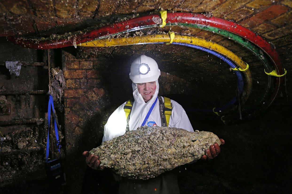"""Tim Henderson, a """"flusher"""" or trunk sewer technician holds a """"fatberg"""" as he works in the intersection of the Regent Street and Victoria sewer in London on December 11, 2014."""
