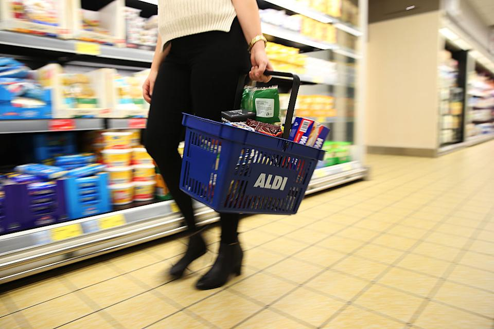 A customer carrying an Aldi Stores Ltd. branded basket walks through one of the company's food stores in Sydney, Australia