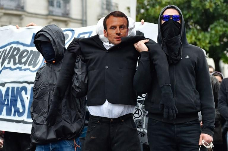 Protestors carry an effigy of French President Emmanuel Macron during a demonstration calling for a union between French rail agent and student protest movements in Nantes western France