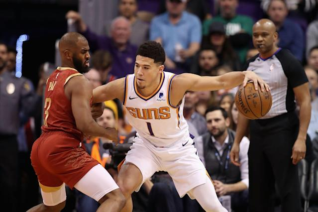 PHOENIX, ARIZONA - FEBRUARY 04: Devin Booker #1 of the Phoenix Suns handles the ball against Chris Paul #3 of the Houston Rockets during the first half of the NBA game at Talking Stick Resort Arena on February 04, 2019 in Phoenix, Arizona. (Photo by Christian Petersen/Getty Images)