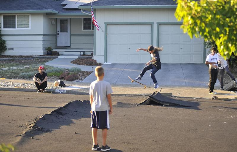 Kids skateboard over buckled roads in a residential neighborhood of Napa, California after an earthquake struck the area on August 24, 2014