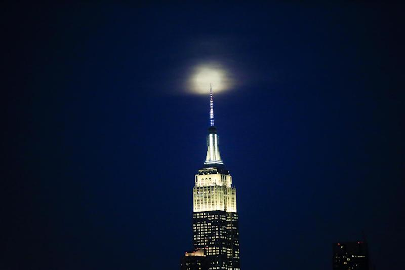 The supermoon is seen above the Empire State Building in New York (REUTERS)