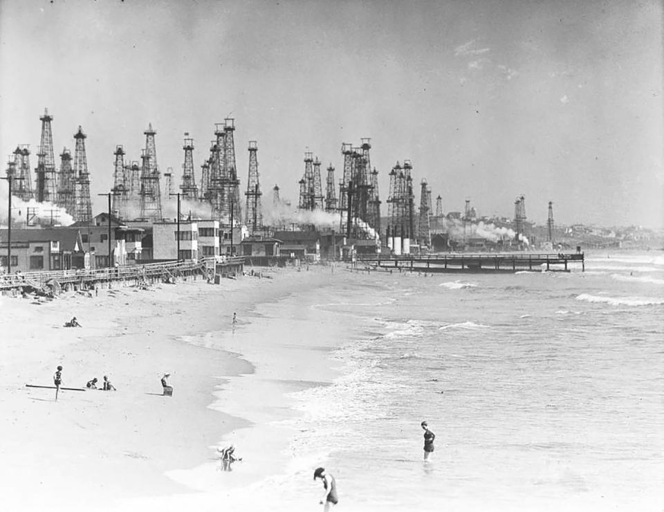In this undated historical image provided by the University of Southern California library, people enjoy the beach in front of an oil field in Playa del Rey, Calif. There are 3.2 million abandoned oil and gas wells in the U.S., according to the Environmental Protection Agency. About a third were plugged with cement, which is considered the proper way to prevent harmful chemical leaks. But most, about 2.1 million by the EPA's count, haven't been plugged at all. (USC via AP)