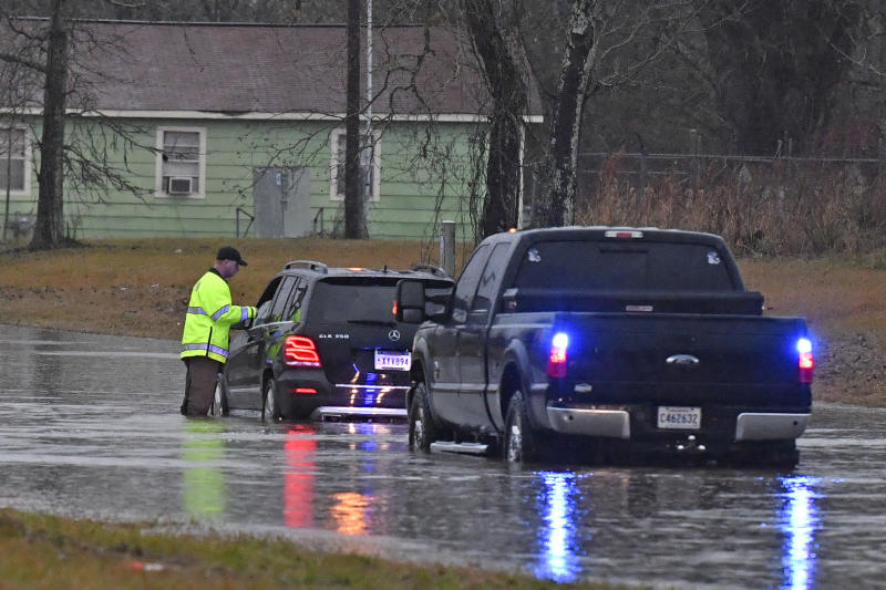 An East Baton Rouge Parish Sheriff's deputy speaks with a stranded motorist on Groom Road near Leland Avenue before pulling the woman to safety, Thursday, Dec. 27, 2018, as severe weather impacts the area in Baker, La. (Hilary Scheinuk/The Advocate via AP)