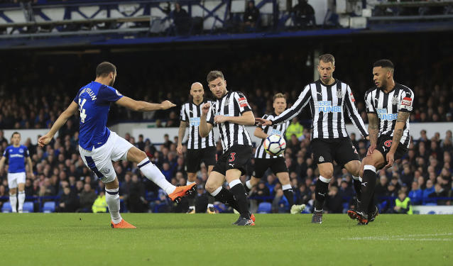 Everton's Cenk Tosun, left, shoots during the English Premier League soccer match between Everton and Newcastle United at Goodison Park, Liverpool, England, Monday, April 23, 2018. (Peter Byrne/PA via AP)