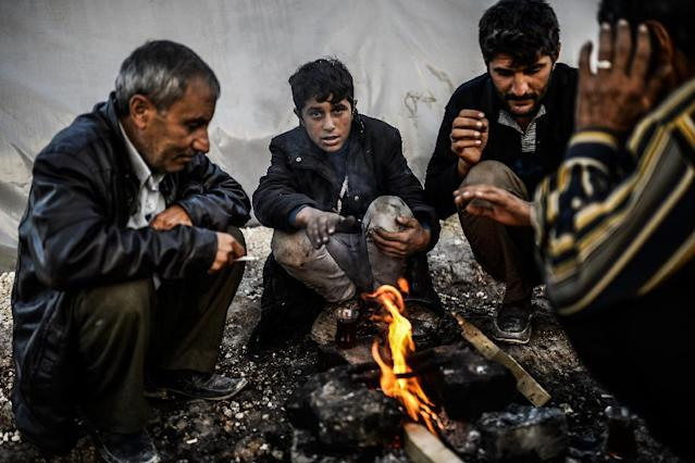 Syrian Kurdish refugees gather around a fire in the Rojava camp in Suruc, in Turkey's Sanliurfa province, on October 22, 2014 (AFP Photo/Bulent Kilic)