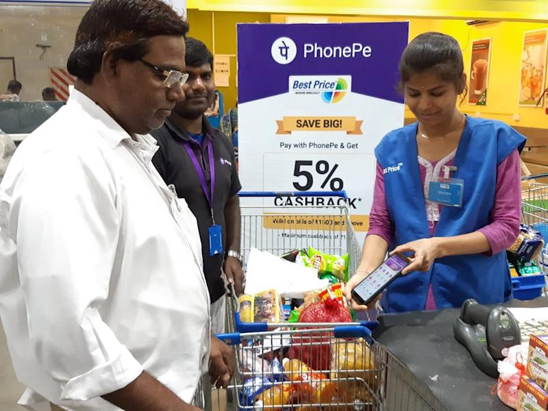 A woman scanning a basket of groceries with a smartphone.