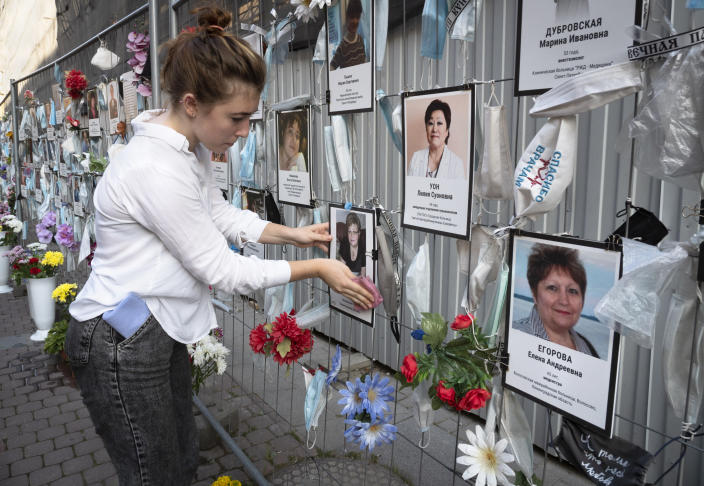 A volunteer dusts off portraits of St. Petersburg's medical workers who died from coronavirus infection during their work, hanging at an unofficial memorial in front of the local health department in St.Petersburg, Russia, Friday, Sept. 25, 2020. The number of daily new cases started to grow in late August in Russia, which has the fourth largest caseload in the world at 1.12 million infections. (AP Photo/Dmitri Lovetsky)