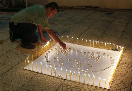 "A man places a candle on a white board spelling out ""MH370"" during a candlelight vigil for the the missing Malaysia Airlines flight, in Kuala Lumpur"