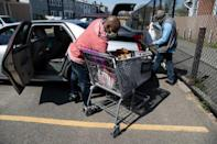 Anthony Lorenzo Green (R) and Bernard Stevenson load groceries into a car for delivery to the needy (AFP Photo/NICHOLAS KAMM)