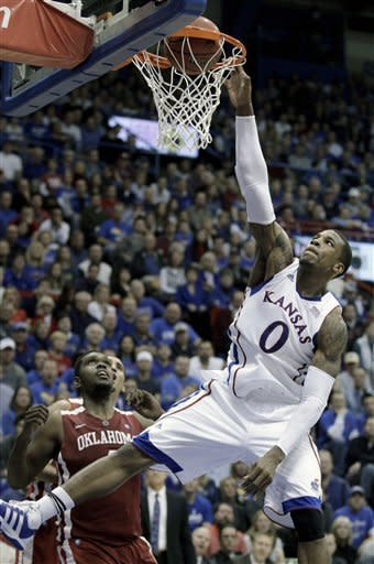 Kansas forward Thomas Robinson (0) gets past Oklahoma forward Andrew Fitzgerald (4) to dunk the ball during the first half of an NCAA college basketball game on Wednesday, Feb. 1, 2012, in Lawrence, Kan. (AP Photo/Charlie Riedel)