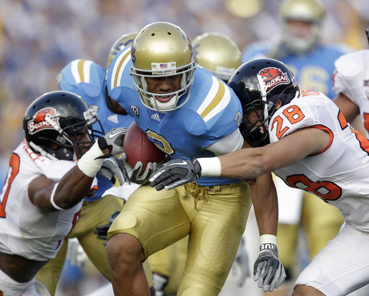 UCLA running back Anthony Barr, center, is tackled by Oregon State safety Suaesi Tuimaunei, right, during the first half of an NCAA college football game at the Rose Bowl in Pasadena , Calif. Saturday, Nov. 6, 2010.