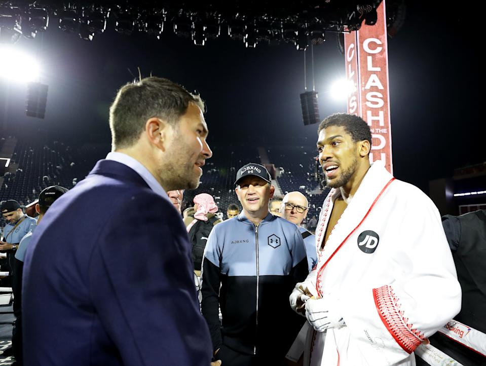 Anthony Joshua chats with promoters Eddie Hearn and Barry Hearn after regaining his IBF, WBA, WBO & IBO World Heavyweight title against Andy Ruiz