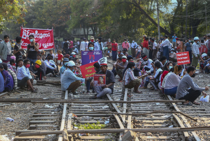 Demonstrators with placards sit on the railway tracks in an attempt to disrupt train service during a protest against the military coup in Mandalay, Myanmar on Wednesday, Feb. 17, 2021. Demonstrators in Myanmar gathered Wednesday in their largest numbers so far to protest the military's seizure of power, even after a U.N. human rights expert warned that troops being brought to Yangon and elsewhere could signal the prospect of major violence. (AP Photo)