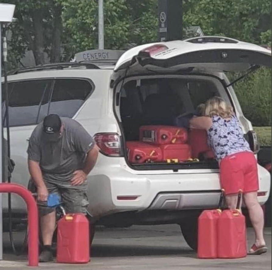 A couple appear to stockpile jerry cans of petrol, loading them into their car.