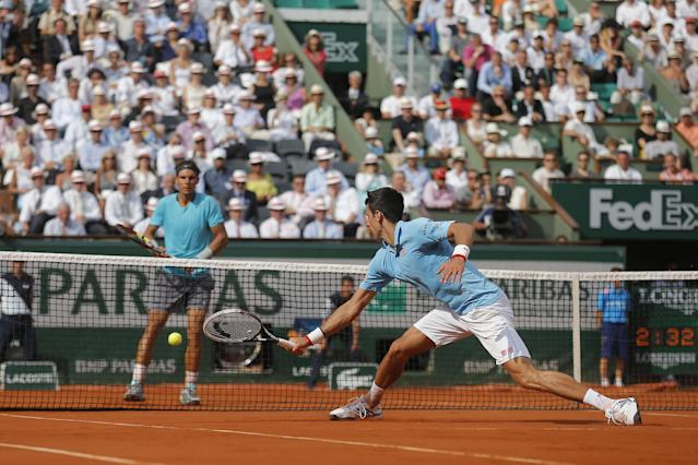 Serbia's Novak Djokovic returns the ball during the final of the French Open tennis tournament against Spain's Rafael Nadal, rear, at the Roland Garros stadium, in Paris, France, Sunday, June 8, 2014. (AP Photo/Michel Spingler)