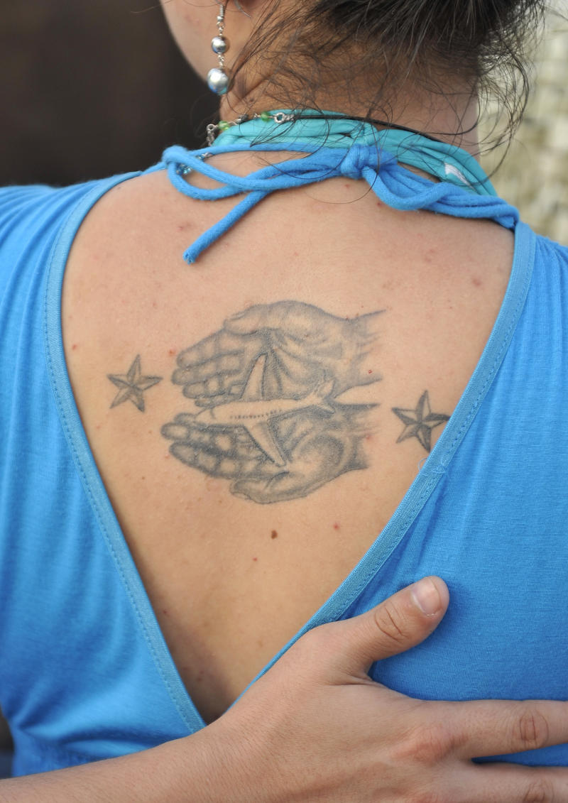 Michelle Hidalgo of Leesburg, Va,  reveals a tattoo on her back in memory of her father, Jim Hull, who was a flight attendant and one of the 230 people killed when a Paris-bound TWA flight 800 jet exploded in the sky off the Long Island coast, Sunday, July 17, 2011 in Shirley, N.Y. Family members and friends gathered to mark the 15th anniversary of the crash at Smith Point County Park on Sunday. (AP Photo/Kathy Kmonicek)