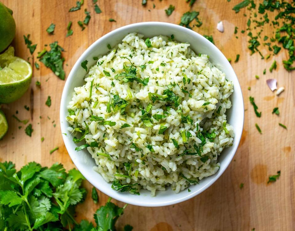 """<p>Talk about a versatile side dish, cilantro lime rice mixes well into <a href=""""https://www.thedailymeal.com/best-burritos-america-gallery?referrer=yahoo&category=beauty_food&include_utm=1&utm_medium=referral&utm_source=yahoo&utm_campaign=feed"""" rel=""""nofollow noopener"""" target=""""_blank"""" data-ylk=""""slk:the best burritos"""" class=""""link rapid-noclick-resp"""">the best burritos</a> and still shines solo. </p> <p><strong><a href=""""https://www.thedailymeal.com/best-recipes/mexican-cilantro-lime-rice?referrer=yahoo&category=beauty_food&include_utm=1&utm_medium=referral&utm_source=yahoo&utm_campaign=feed"""" rel=""""nofollow noopener"""" target=""""_blank"""" data-ylk=""""slk:For the Cilantro Lime Rice recipe, click here."""" class=""""link rapid-noclick-resp"""">For the Cilantro Lime Rice recipe, click here.</a></strong></p>"""