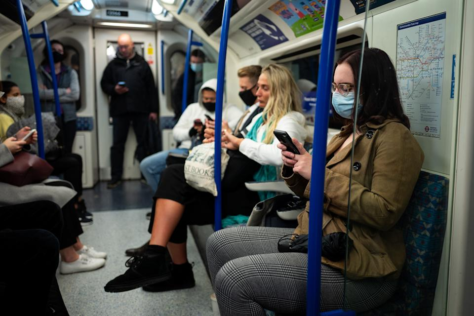 Commuters, most wearing masks because of the coronavirus pandemic, travel on a London Underground