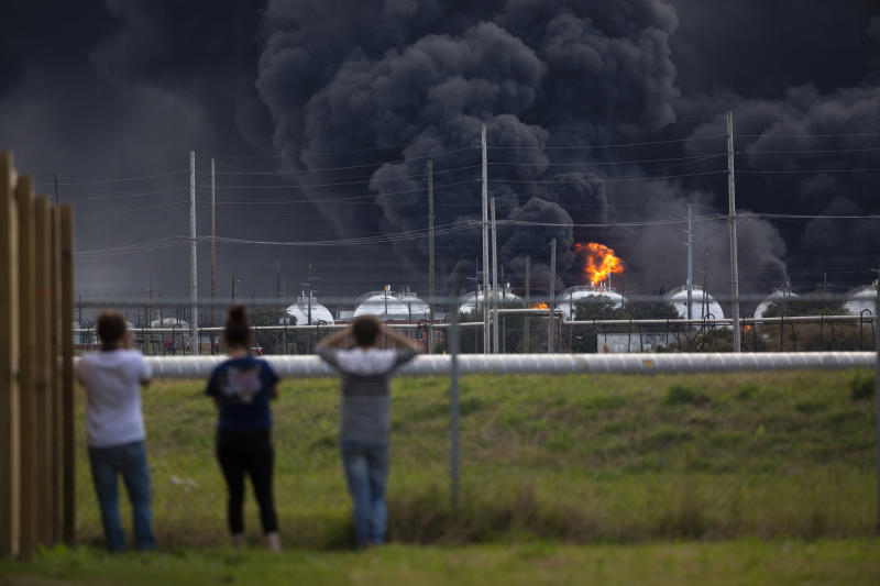 Residents observe the fire consuming the TPC Group plant on Wednesday, Nov. 27, 2019, in Port Neches, Texas.  Two massive explosions 13 hours apart tore through the chemical plant Wednesday, and one left several workers injured. (Marie D. De Jesús/Houston Chronicle via AP)