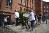 Voters queue outside a polling station in Wittenberg, Germany Sunday June 6, 2021 for the state election in Saxony-Anhalt. The election for the new state parliament in Saxony-Anhalt is the last state election before the federal election in September 2021. (Robert Michael/DPA via AP)