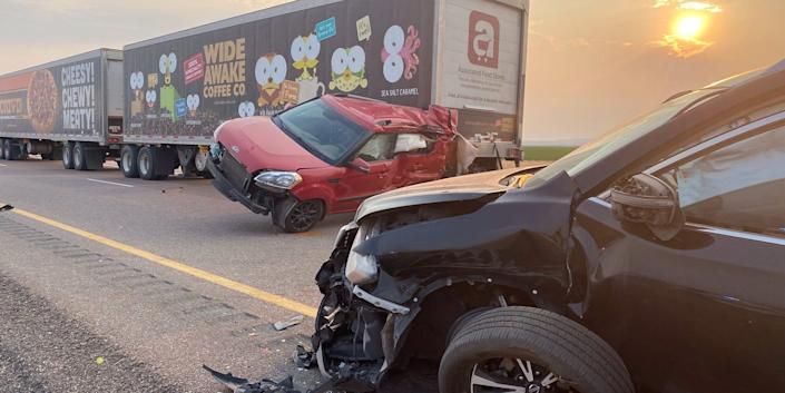 Two cars and a truck on a road, with some damage