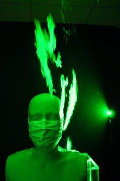 A mannequin wearing a mask lit by green light revealing cloud of vapour leaking from mask.