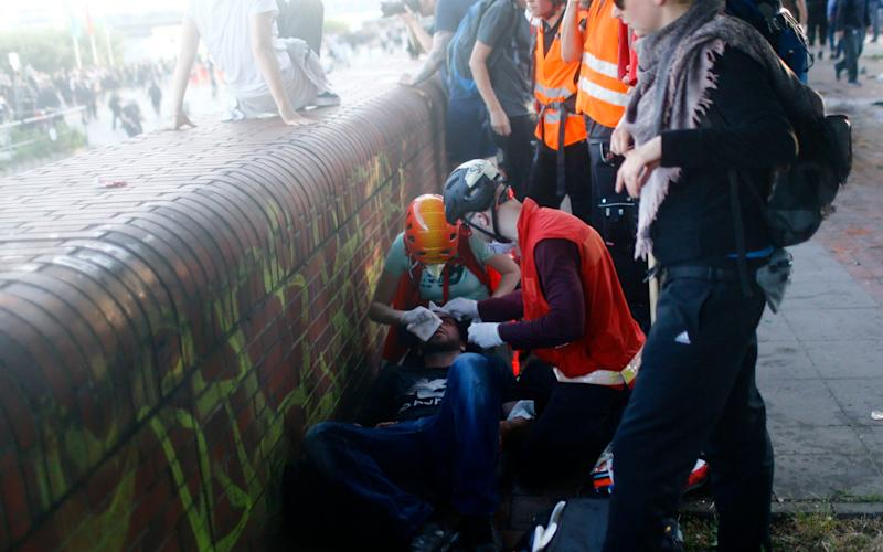 An injured protester gets help during the demonstration during the G20 summit in Hamburg - Credit: Reuters