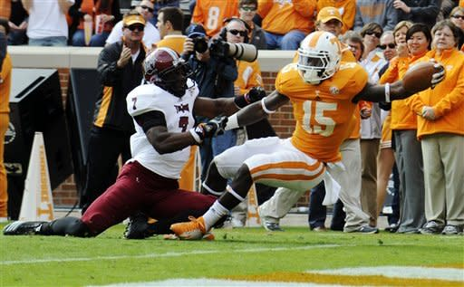 Tennessee running back Marlin Lane (15) rips away from Troy defensive back Chris Pickett (7) to score a touchdown during the first half of their NCAA college football game, Saturday, Nov. 3, 2012, in Knoxville, Tenn. (AP Photo/Knoxville News Sentinel, Amy Smotherman Burgess)