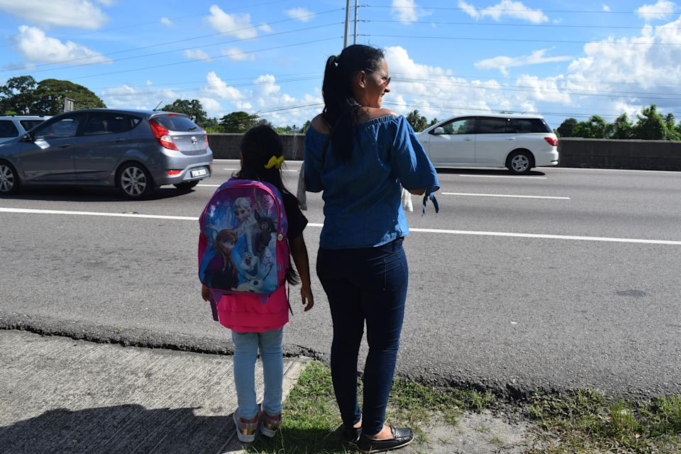 Ruth Navarro and her daughter, Stephani, both Venezuelan, wait for a bus on the outskirts of Port of Spain, Trinidad. Stephani is taking classes at a space run by a local non-profit, but it's not a school and isn't accredited by the Ministry of Education. Under current rules, the children of undocumented migrants in Trinidad cannot attend public school. (Jim Wyss/Miami Herald/Tribune News Service via Getty Images)