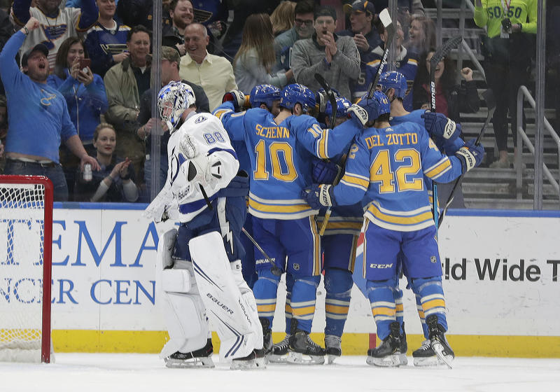 St. Louis Blues' Brayden Schenn (10) and Michael Del Zotto (42) celebrate with teammates after a goal by Vladimir Tarasenko (91) as Tampa Bay Lightning goaltender Andrei Vasilevskiy (88) skates past in the first period of an NHL hockey game, Saturday, March 23, 2019, in St. Louis. (AP Photo/Tom Gannam)